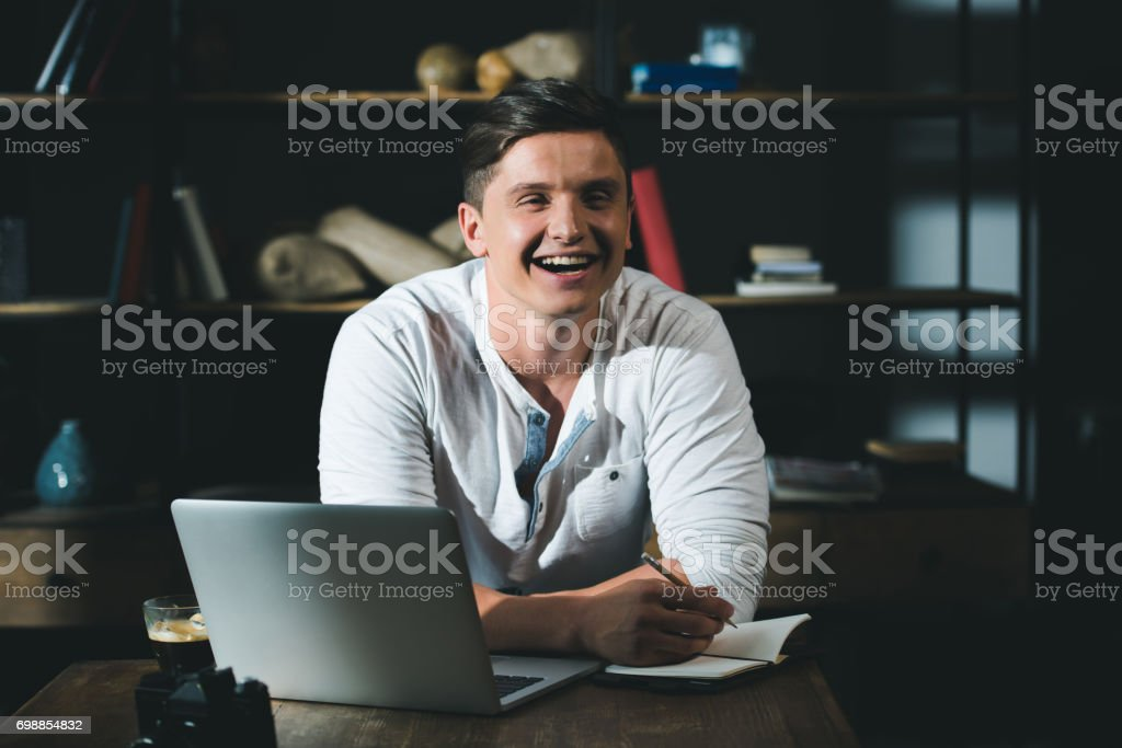 Stylish man in good mood taking notes during work at modern workplace stock photo