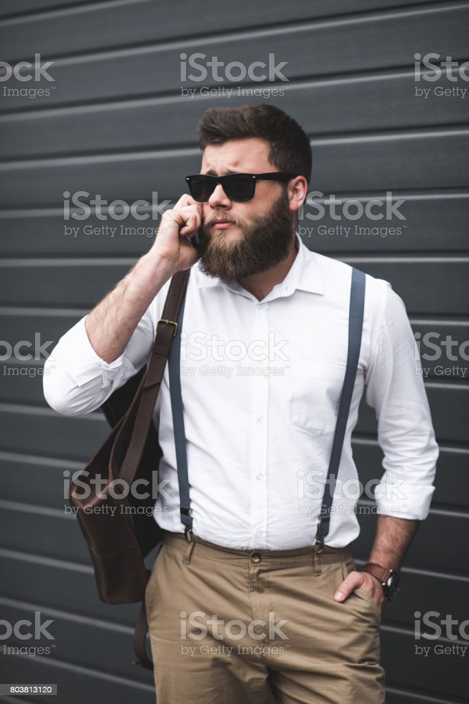 stylish man in sunglasses and suspenders using smartphone and looking away stock photo