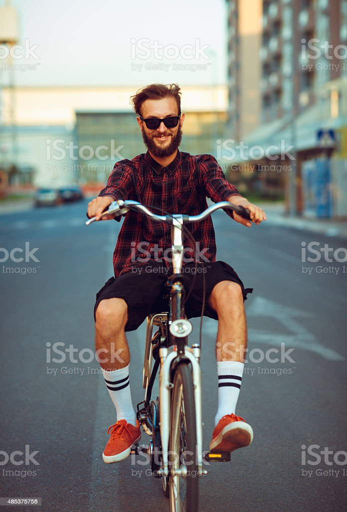 Stylish man in sunglasses riding a bike on city street stock photo