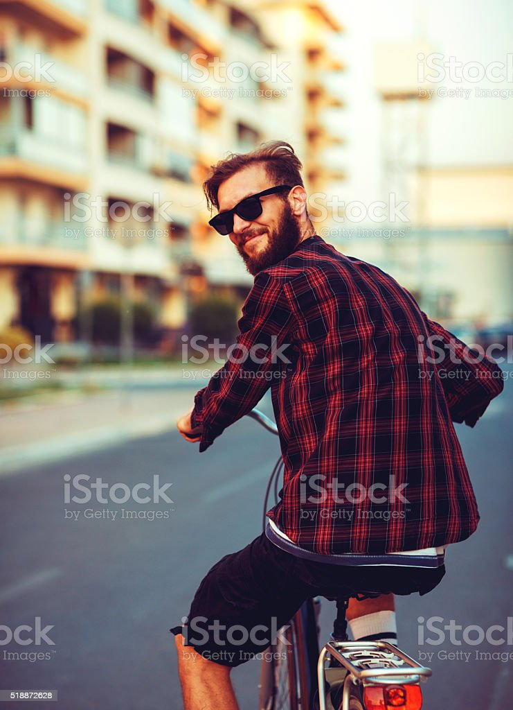 Stylish man in sunglasses riding a bike on city street stock photo