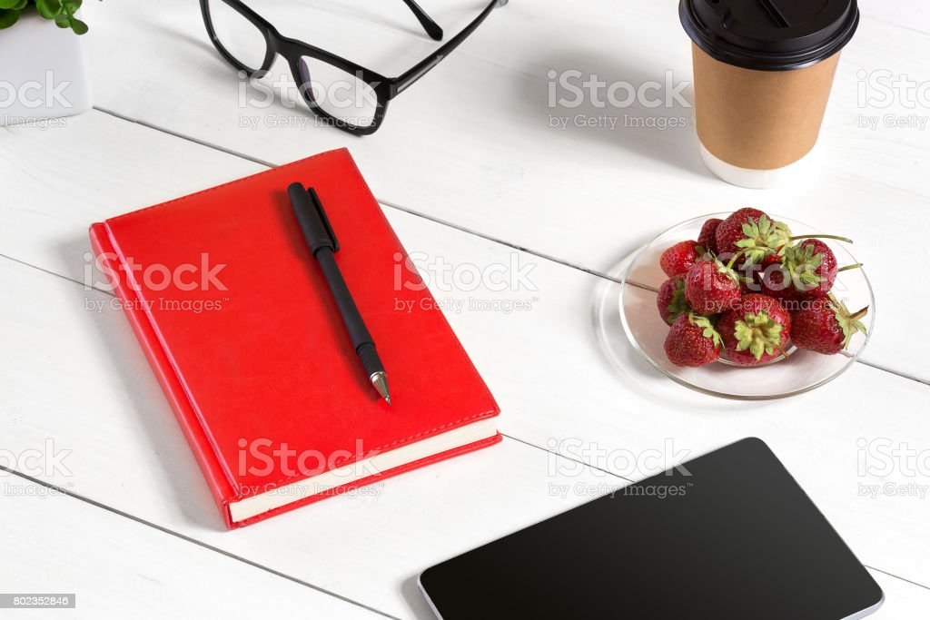Stylish minimalistic workplace with tablet and notebook and glasses in flat lay style. White background stock photo