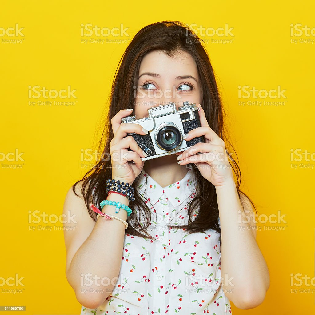 Stylish modern girl posing with a retro camera in hands stock photo