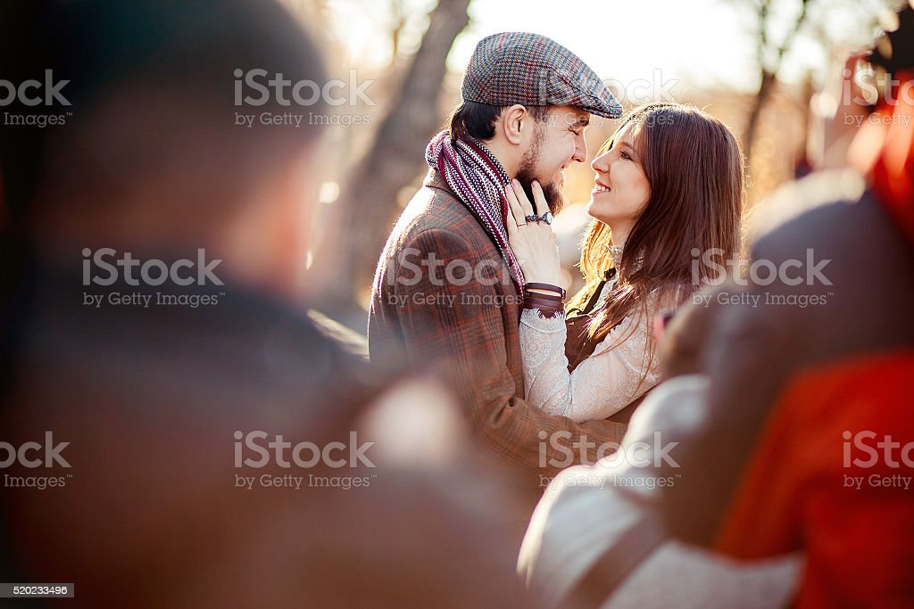 Stylish old fashioned couple among crowd looking at each other stock photo