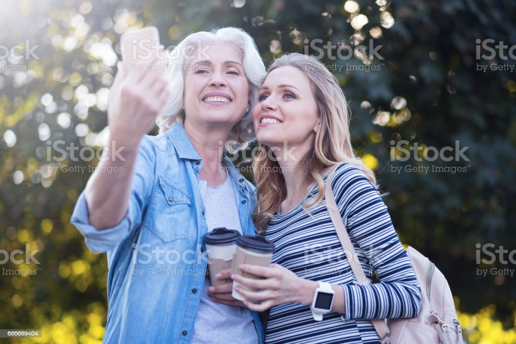 Stylish old woman taking selfie with pregnant daughter outdoors stock photo