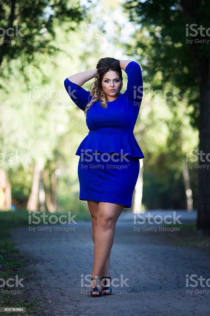 Stylish plus size fashion model in dress outdoors, xxl woman stock photo