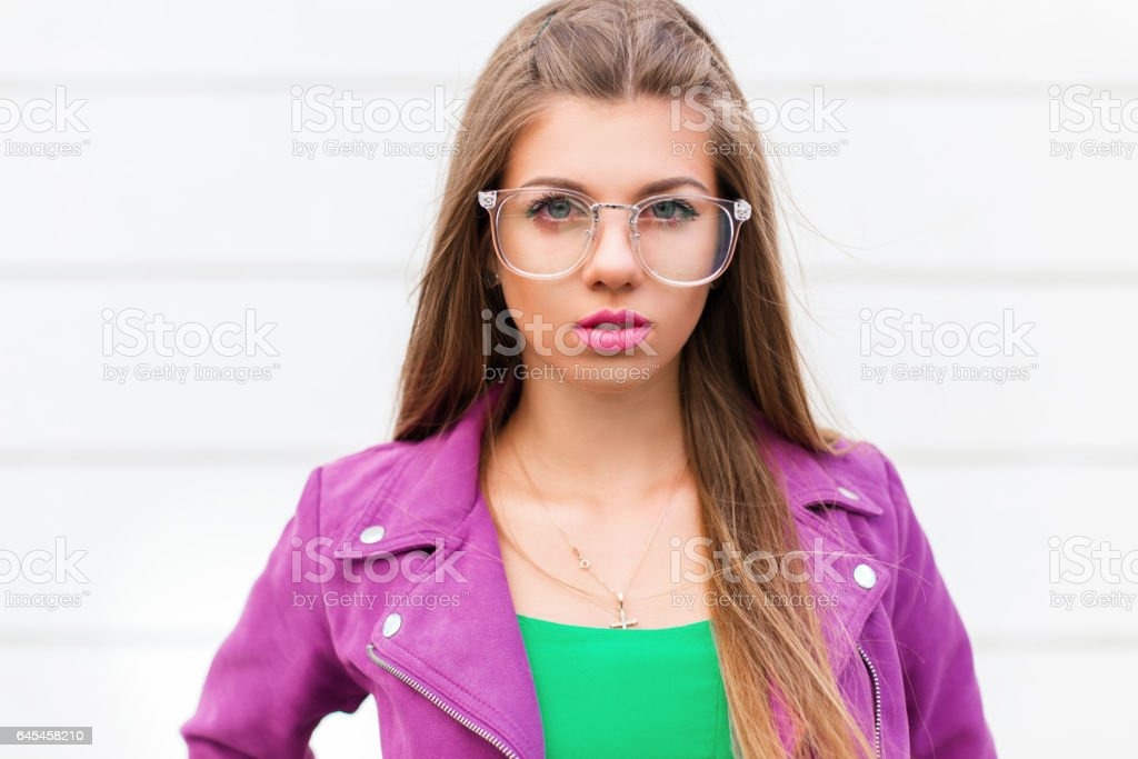 Stylish portrait of a beautiful young woman in a purple jacket with sunglasses near a white wall stock photo