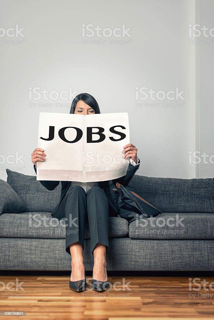 Stylish professional woman reading the Jobs ads stock photo