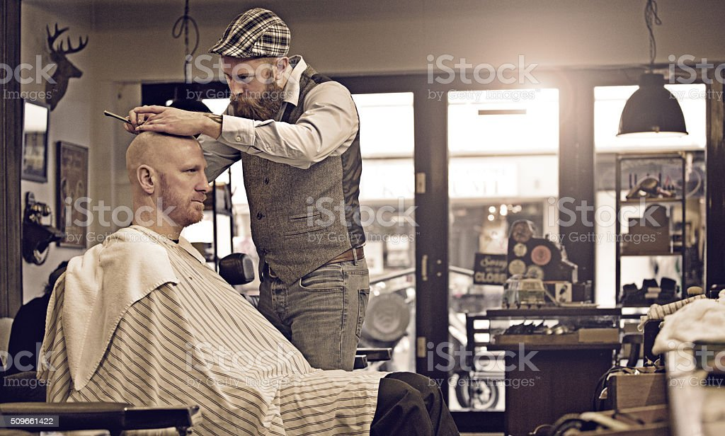 Stylish retro bearded barber with a bearded bald male client stock photo