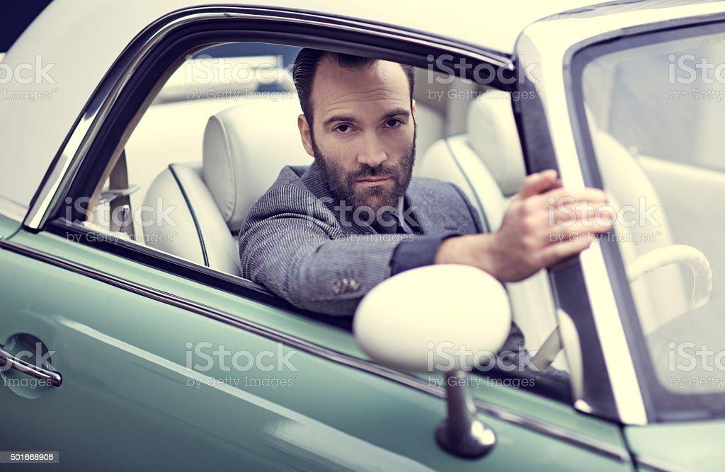Stylish retro dressed man driving vintage car stock photo