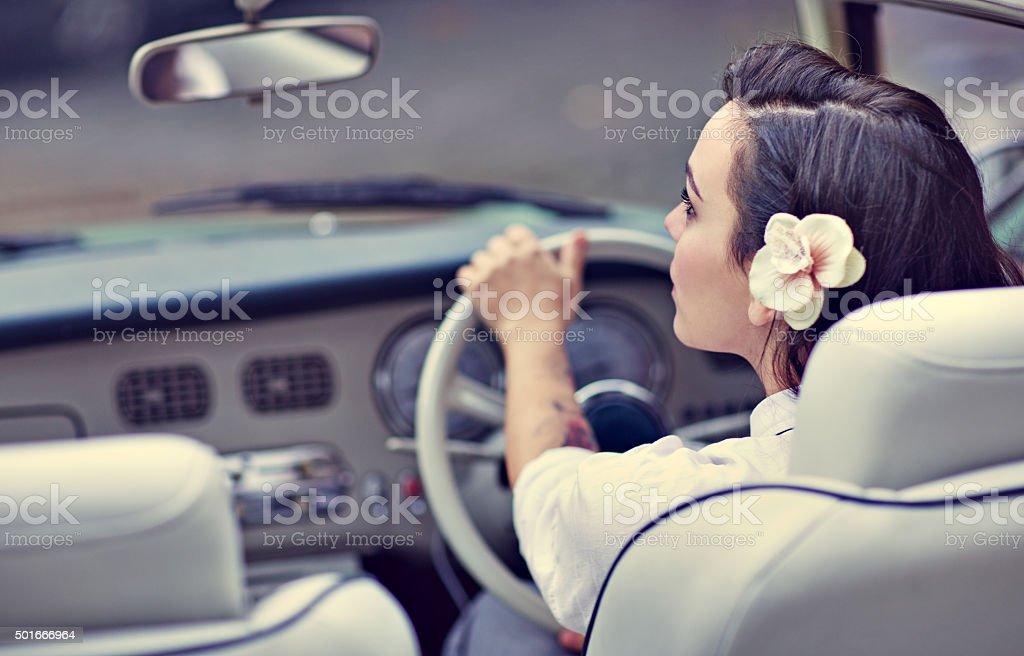 Stylish retro dressed woman driving vintage car stock photo