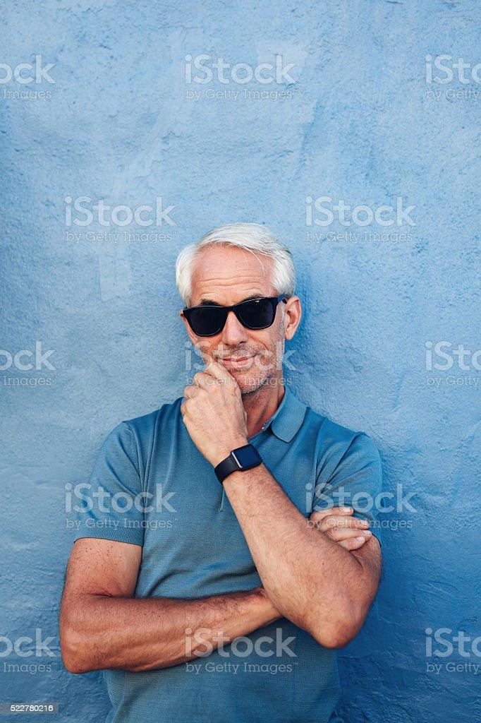 Stylish senior man with sunglasses and smart watch stock photo