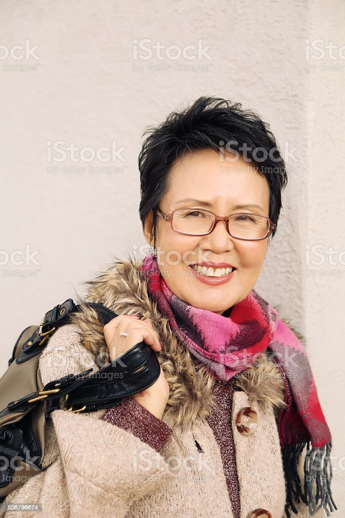 Stylish Senior Woman Leaning Against a Wall stock photo