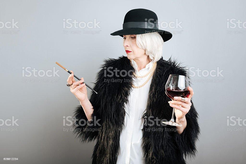 Stylish serious lady holding cigarette and wineglass. stock photo