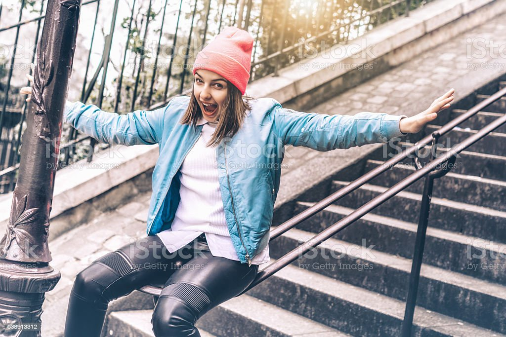 stylish teenage girl slipping down ballustrade of monmartre stairs stock photo