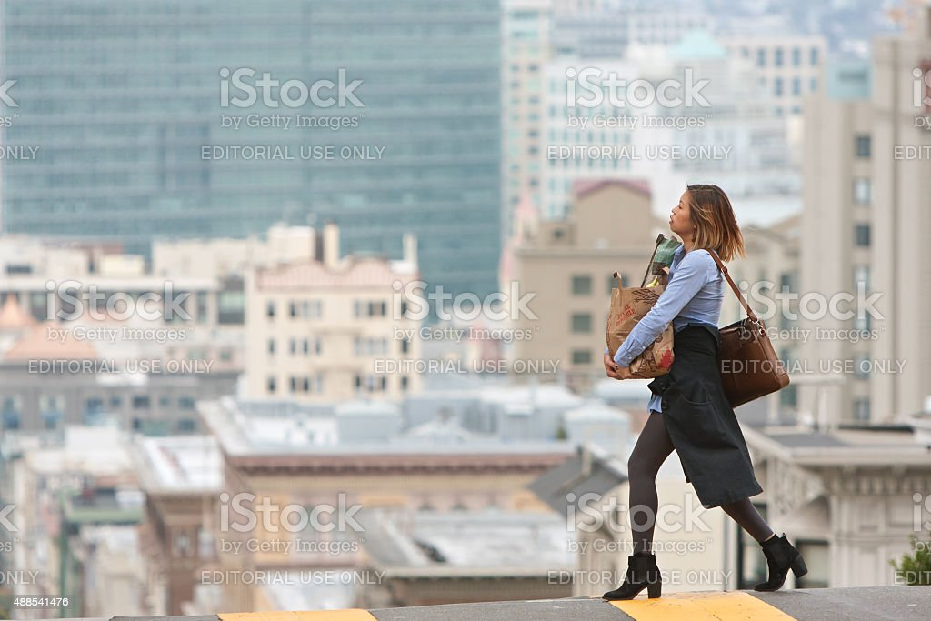 Stylish Woman Carrying Groceries Crosses Scenic San Francisco Street stock photo