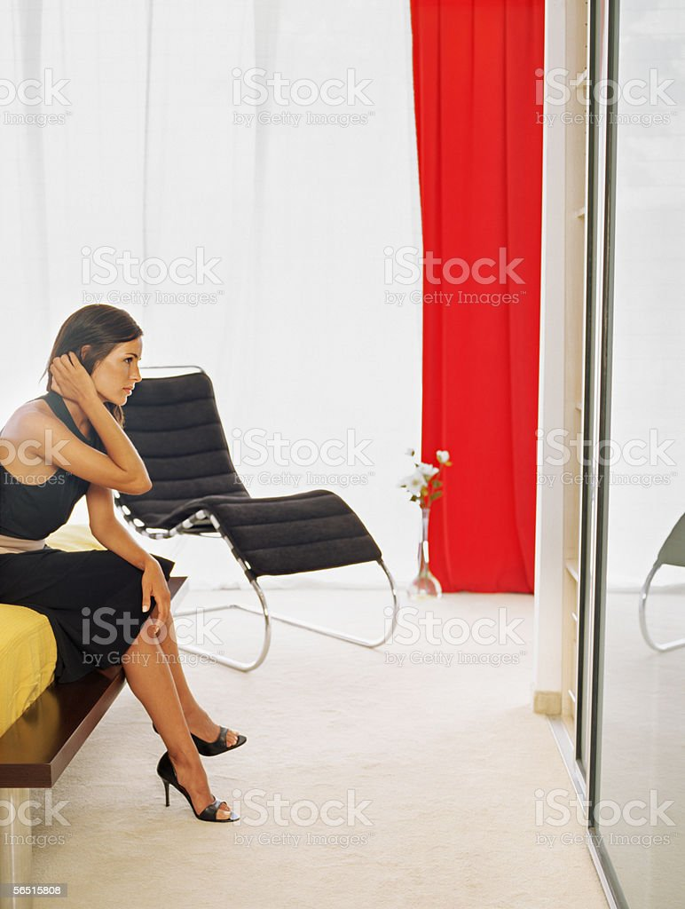 Stylish woman sitting on a bed royalty-free stock photo