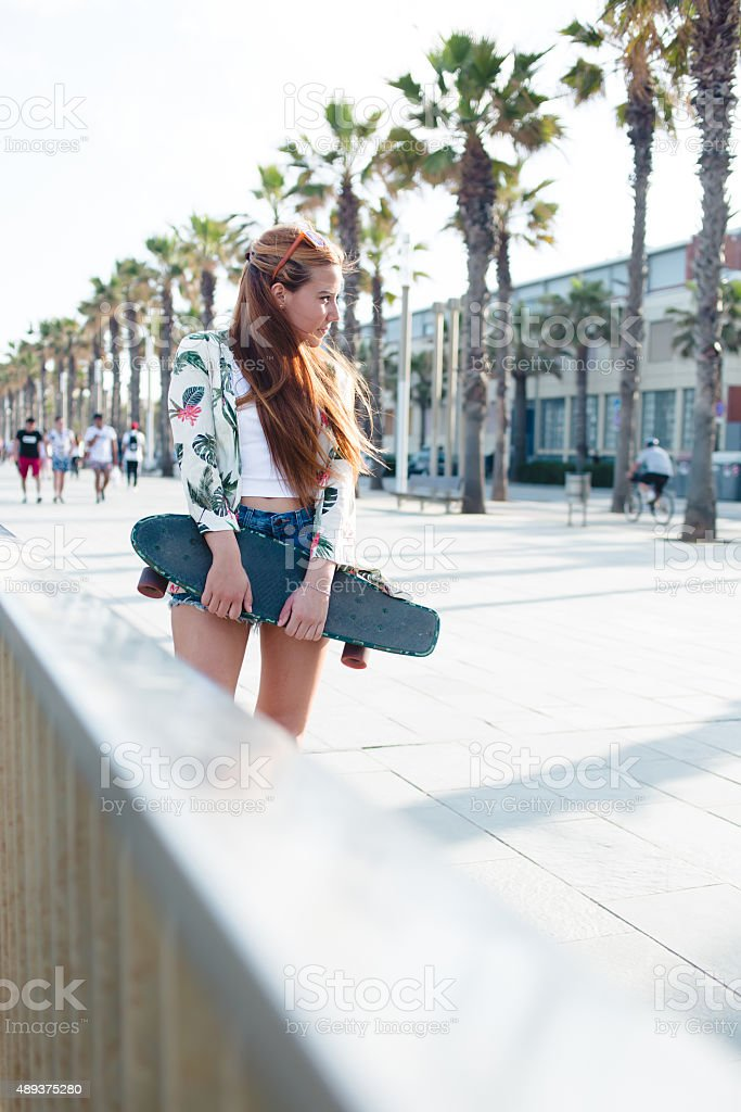 Stylish woman skateboarder standing with her penny board outdoors stock photo