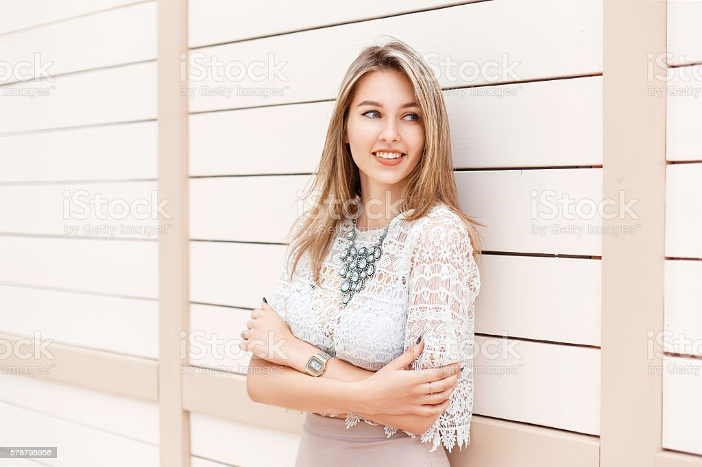 Stylish woman smiling in lace blouse and dress near wall. stock photo