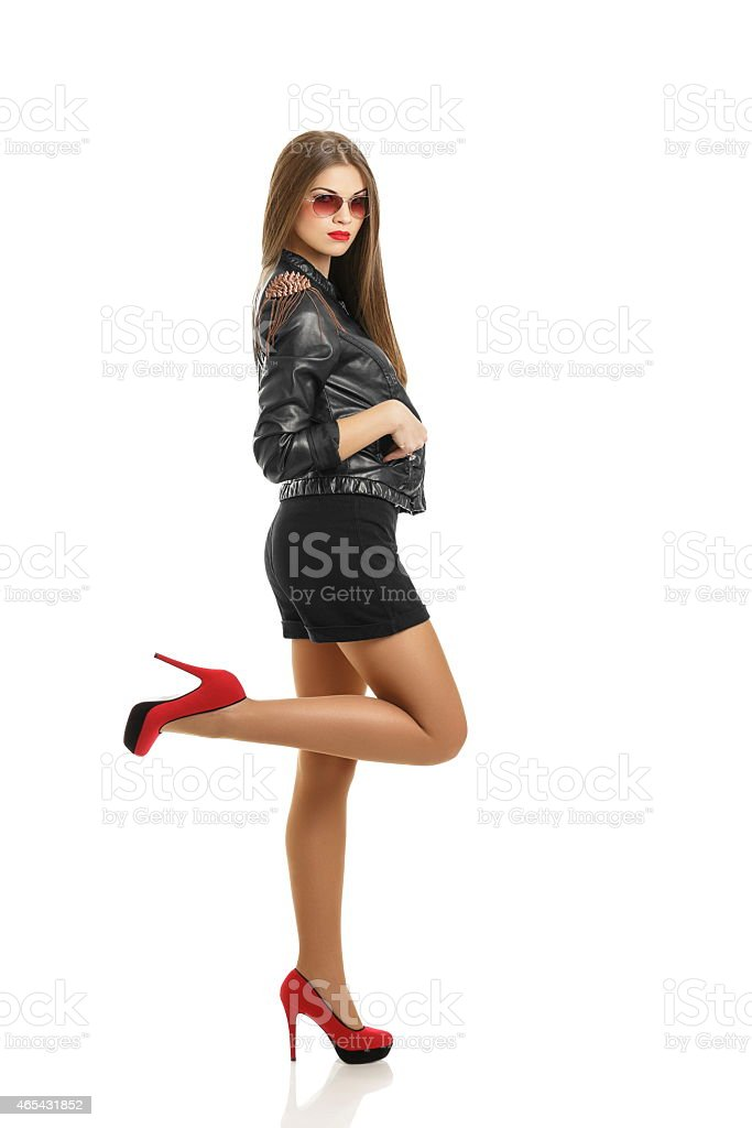 Stylish woman wearing red high heels and a leather jacket stock photo