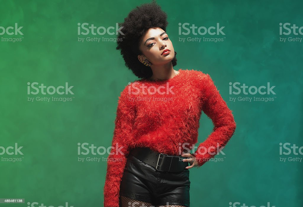 Stylish Woman with Afro Hair Against Green Wall stock photo