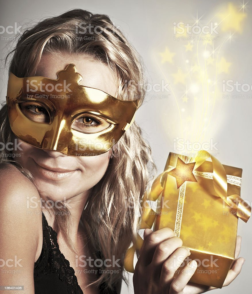 Stylish woman with golden mask and gift royalty-free stock photo