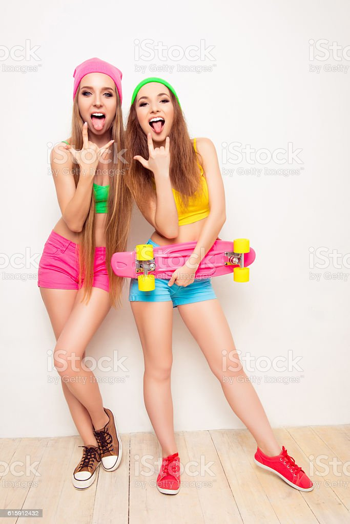Stylish woman with skateboard showing tongues and rock gesture stock photo