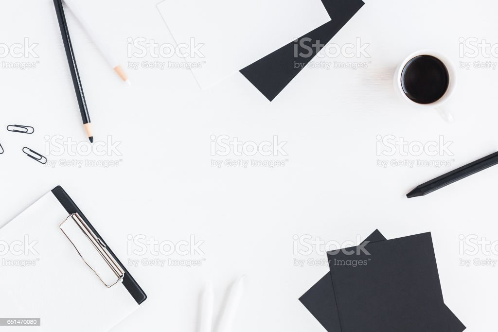 Stylish workspace with notebook, cup of coffee, paper blank, pencils....