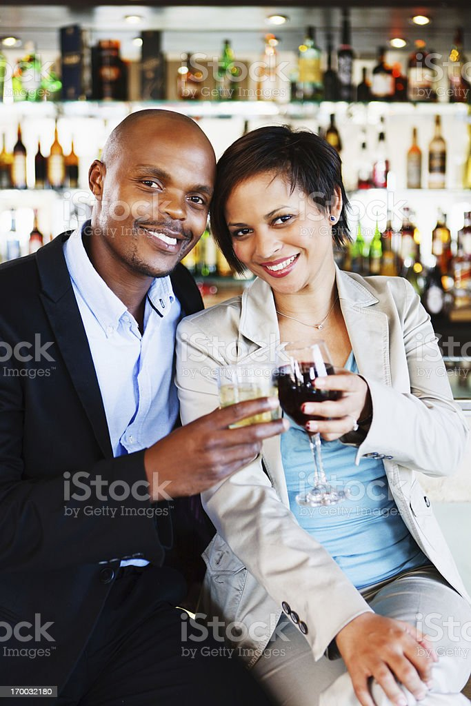 Stylish young couple toasting in red wine at upmarket bar royalty-free stock photo