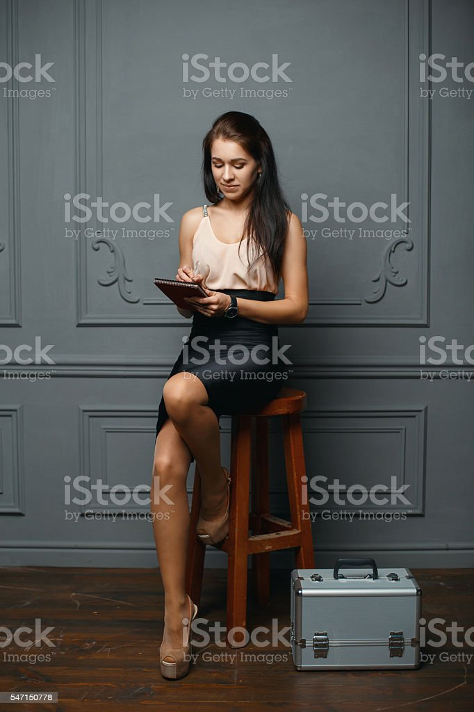 Stylish young girl sitting on a wooden chair, writing stock photo
