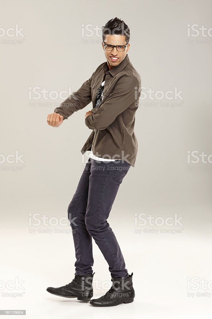 Stylish young man dancing over grey background royalty-free stock photo