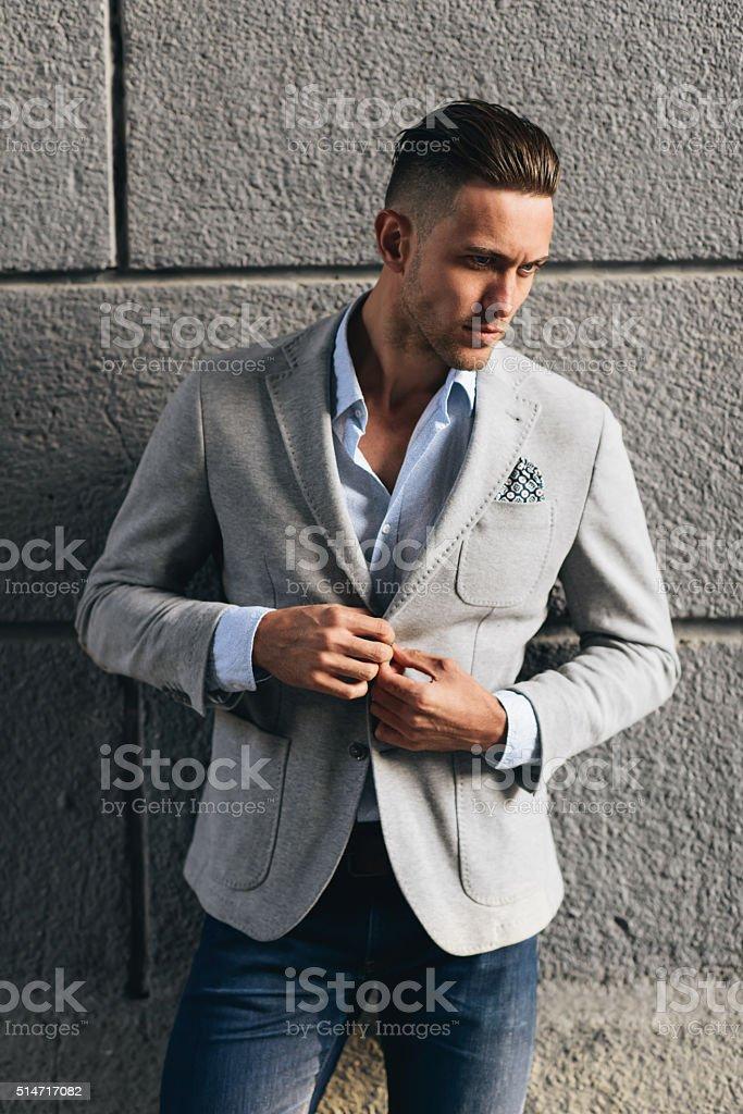 Stylish young man poising near the wall stock photo