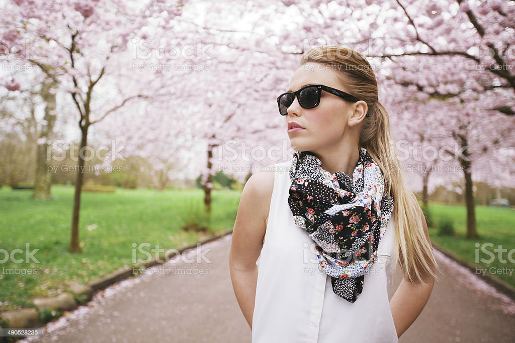 Stylish young woman posing at the spring blossom garden. stock photo