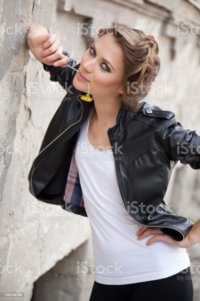 Stylish young woman smiling, posing with dandelion outdoors royalty-free stock photo