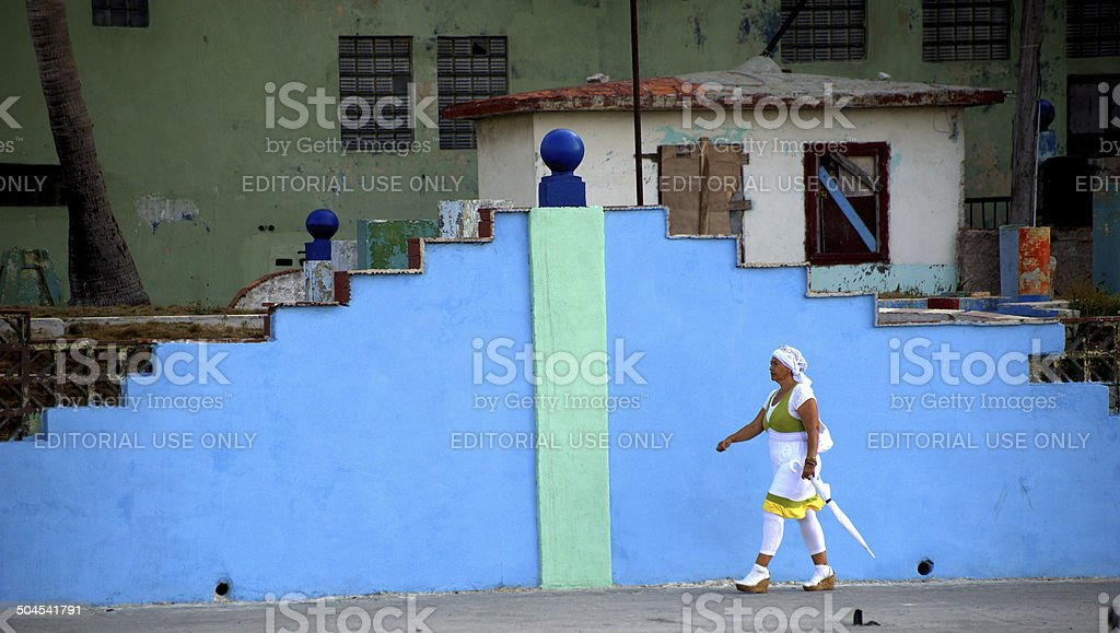 Stylishly dressed woman walking by art deco wall in Havana, stock photo