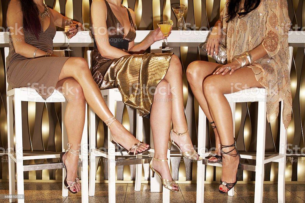 Stylishly Dressed Women Sitting At The Bar stock photo