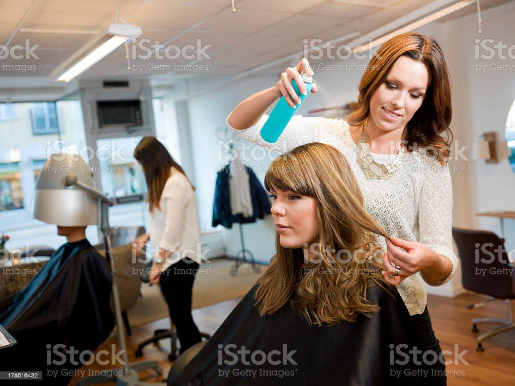 Stylist finishing a woman's haircut at a beauty salon stock photo