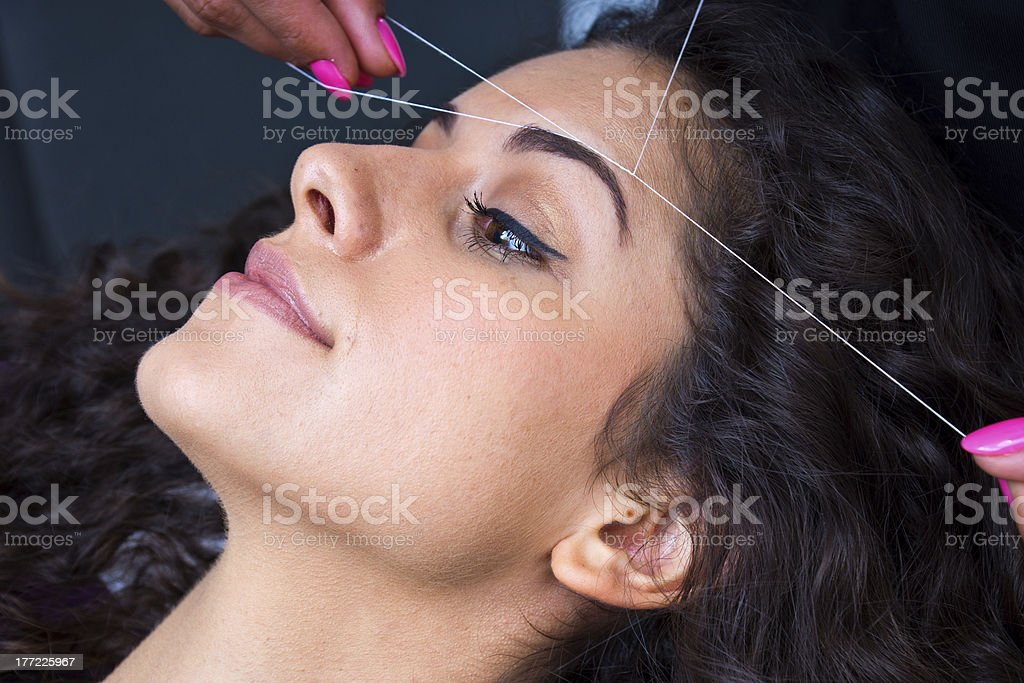 A stylist in a salon threading a brow of a woman stock photo