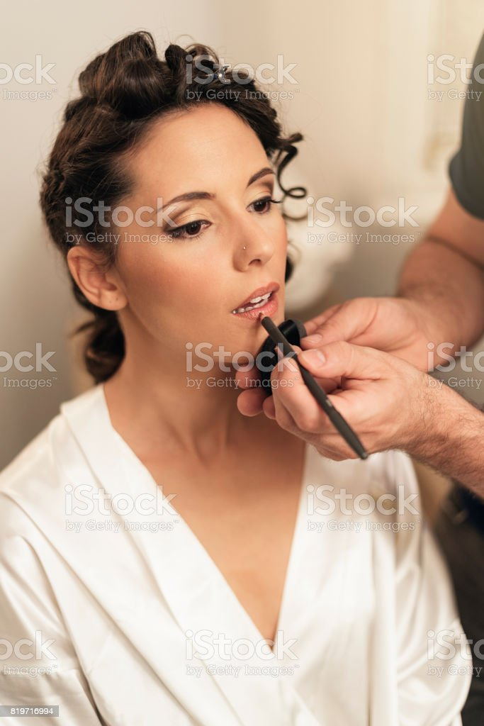 Stylist makes makeup bride on the wedding day. stock photo