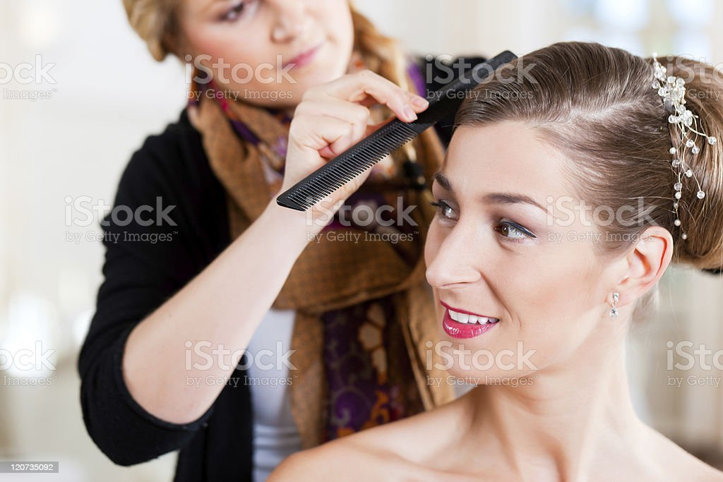 Stylist pinning up a bride's hairstyle royalty-free stock photo