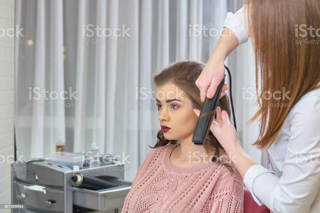 Stylist using hair straightener. stock photo
