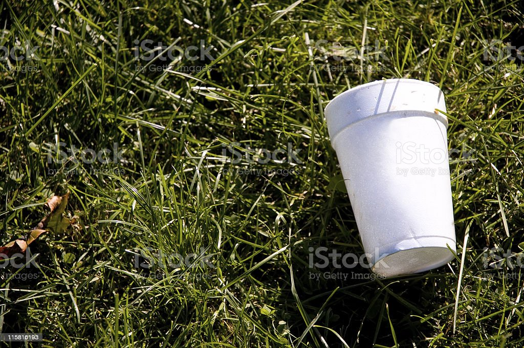 A styrofoam cup on the grass representing litter royalty-free stock photo