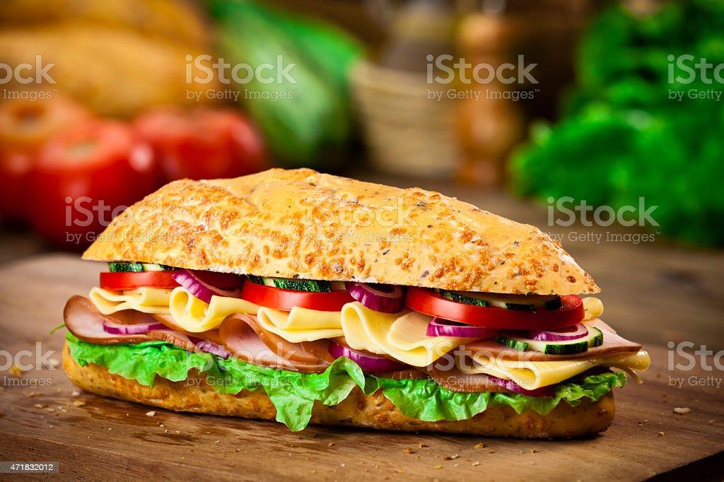 Submarine sandwich on rustic wood table stock photo
