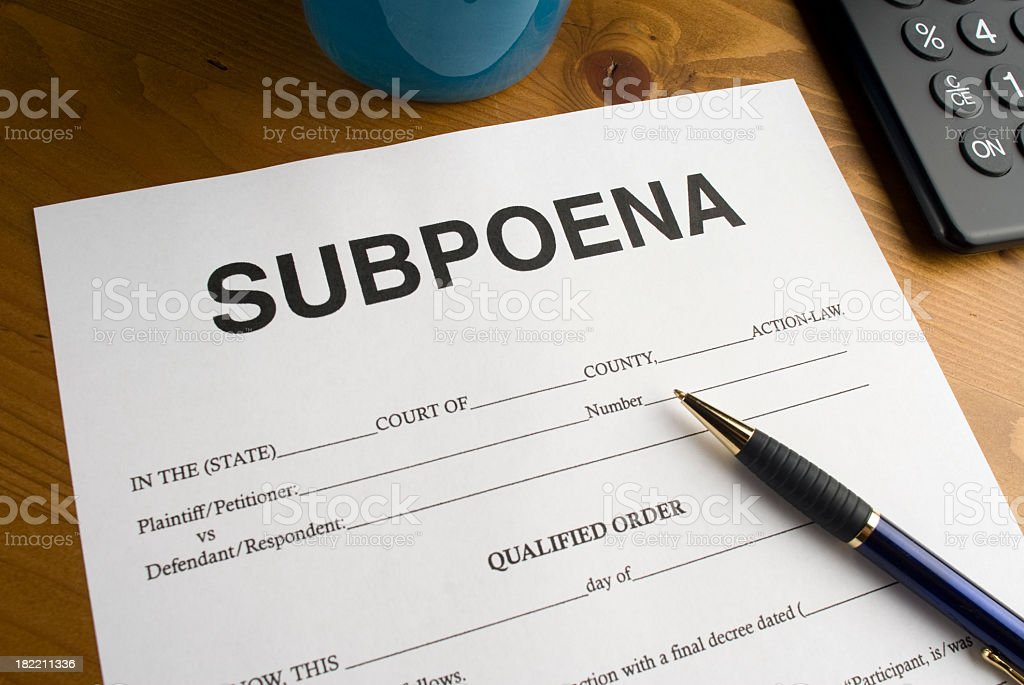 Subpoena form with a pen on a wooden desk royalty-free stock photo