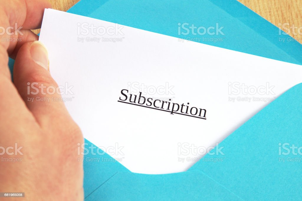 Subscription printed on white paper and blue envelope, hand holding it, wooden background stock photo