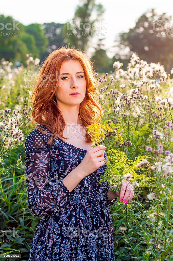 Subtle woman stands on a flowery meadow stock photo