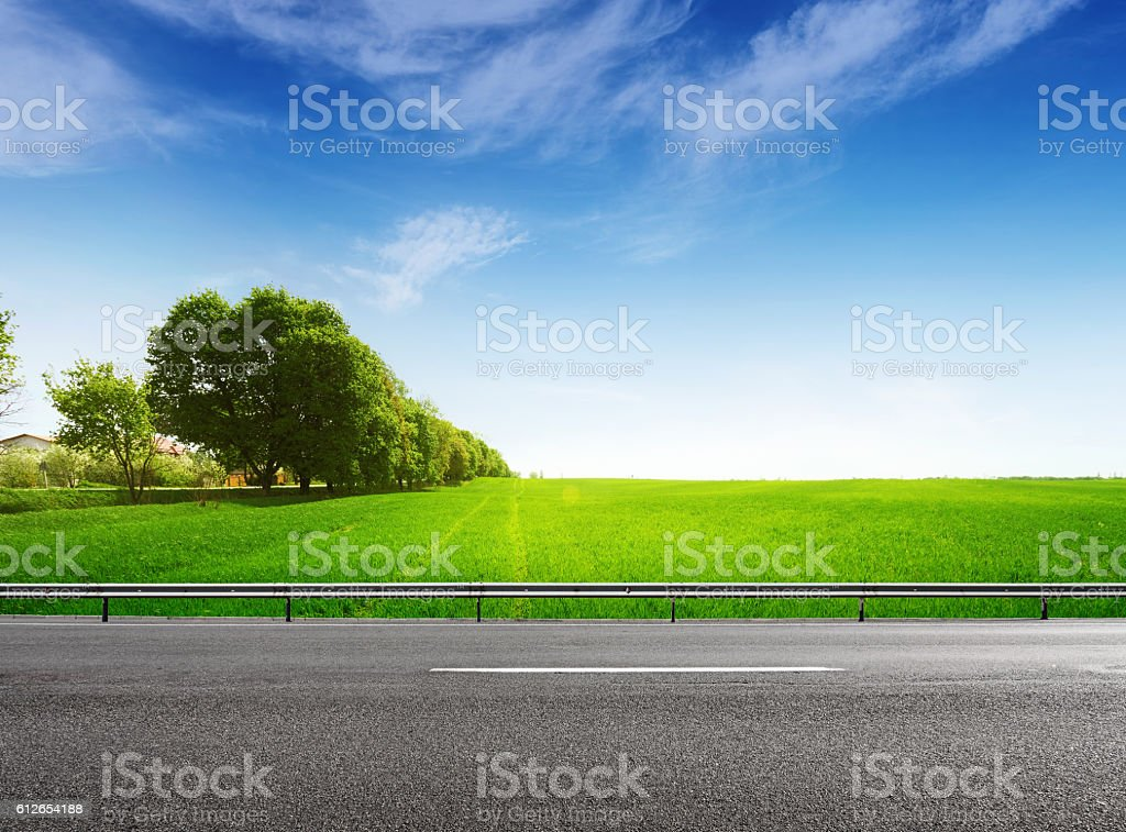 Suburb asphalt road and green field stock photo