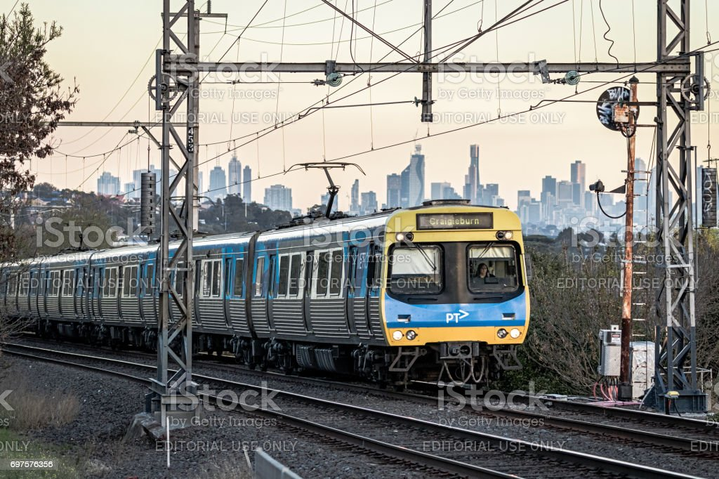 Suburban commuter train heads away from downtown Melbourne city stock photo