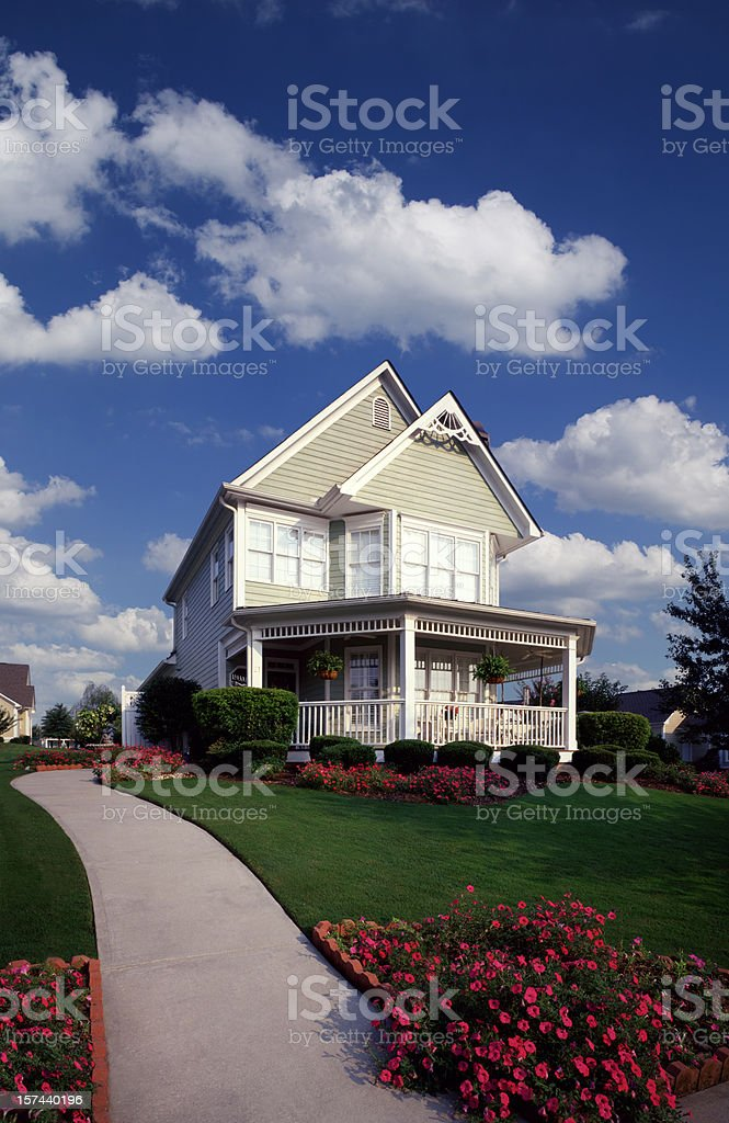 Suburban Home with Garden and fluffy clouds stock photo
