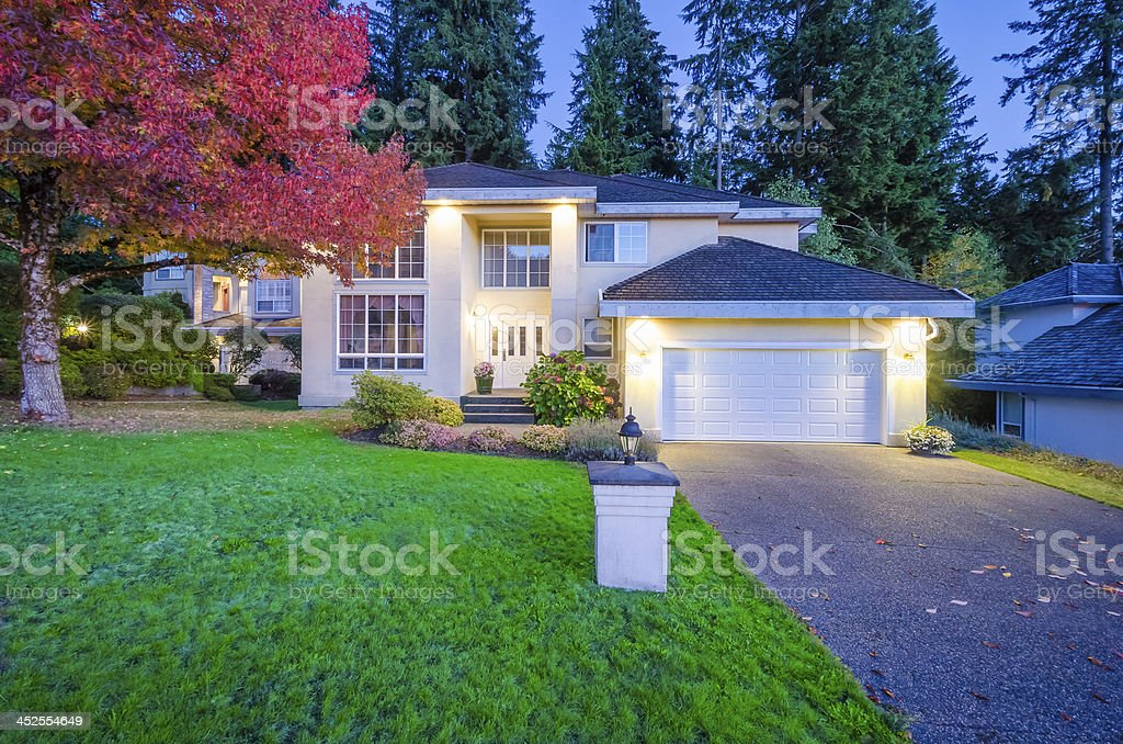 Suburban house at nighttime with lights stock photo