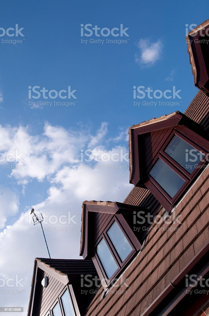 Suburban House Roof Against The Blue Cloudy Sky royalty-free stock photo
